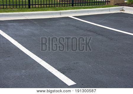 empty parking space in lot with white lines and curb