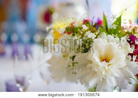 Bright decor of a wedding feast made of fresh juicy flowers on a blurred background