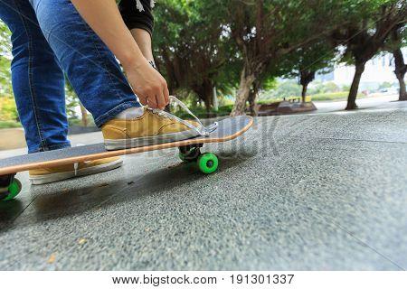 young skateboarder tying shoelace skateboard at city skatepark