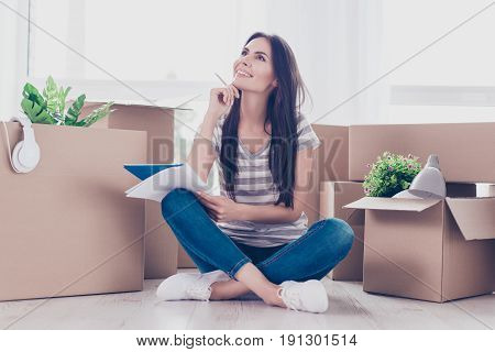Cute Teen In Casual Clothes Is Sitting With Crossed Legs On The Floor. A Lot Of Unpacked Boxes Near