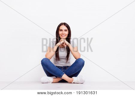 Cute Smiling Young Girl Is Sitting On The Floor With Crossed Legs And Holds Her Head With Hands. Beh