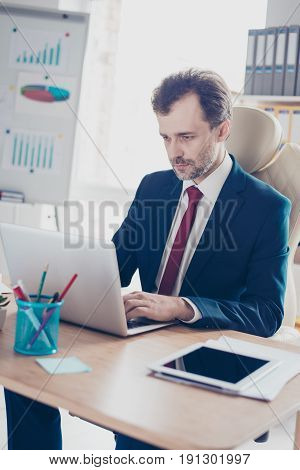 Close Up Portrait Of Busy Realtor Typing At His Laptop In The Modern Office. He Is Wearing Formalwea