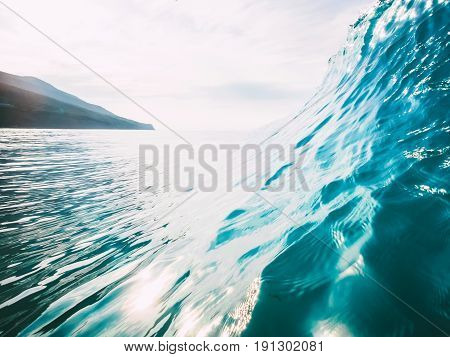 Blue big wave, cloudy sky and coast