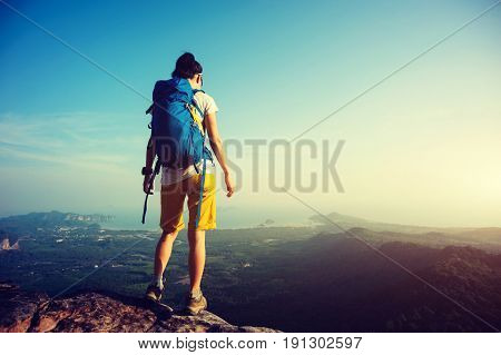 successful woman backpacker looking down on mountain top rock