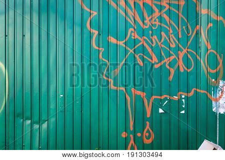 Red chaotic lines drawn on a green metal fence