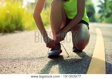 fitness woman runner tying shoelace on forest trail
