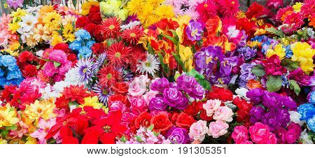 A variety of artificial flowers. Colorful background of flowers