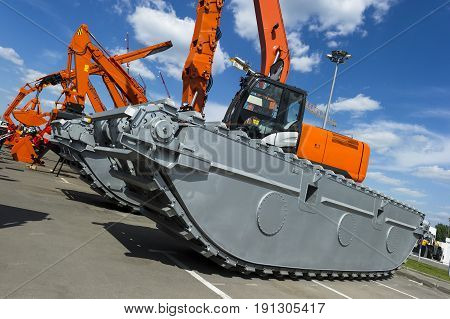 Bulldozer, excavator and other orange construction machines with scoop, shovel, jackhammer and another equipment in row, heavy industry, blue sky and white clouds on background