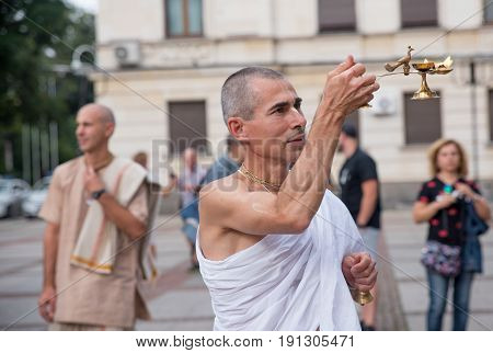 SofiaBulgaria - September 10 2016: The cart festival called 'Ratha Yatra' in Sofia september 10 2016. Priests throw fruits offered to the deities to the people lifting up their hands to catch them.