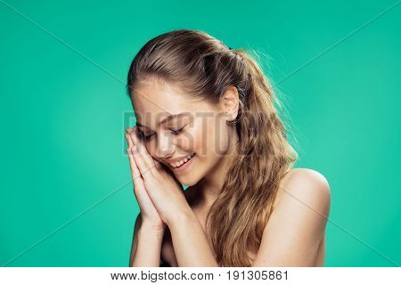 Woman leaning hands to face, woman smiling on green background portrait.