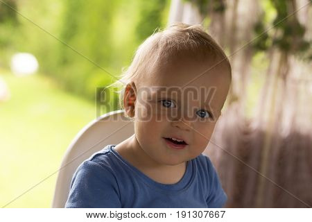 Adorable toddler sitting outdoor in a baby chair, smiling and looking at camera.
