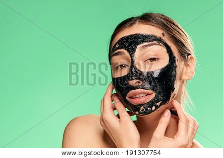 Face care, skin problem, woman in cosmetic mask on green background.