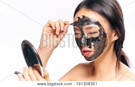 Woman lifting a make-up mask from the face, a woman holding a mirror on an isolated background.
