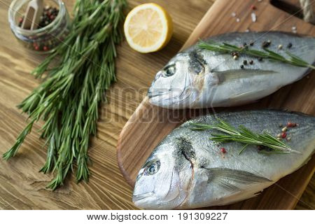 Raw fish cooking and ingredients. Dorado, lemon, herbs and spices on wooden background.