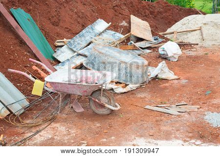 Grunge Red Wheelbarrow with Construction Tools and Material with Background of Soil and steel bar