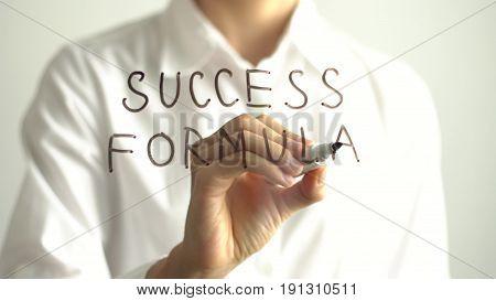 Woman writing Success Formula on transparent screen.Businesswoman write on board. Success concept.