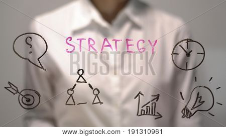 Woman wrote Strategy on transparent screen. Businesswoman write on board. Drawing on desk.