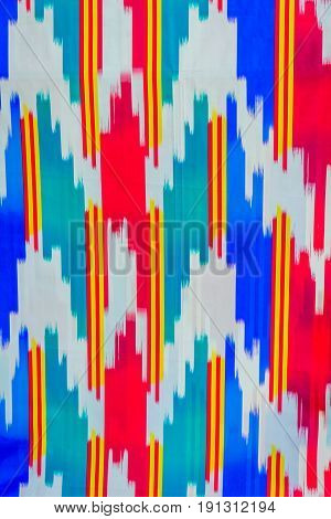 Traditional colorful Uzbek pattern on the fabric close up