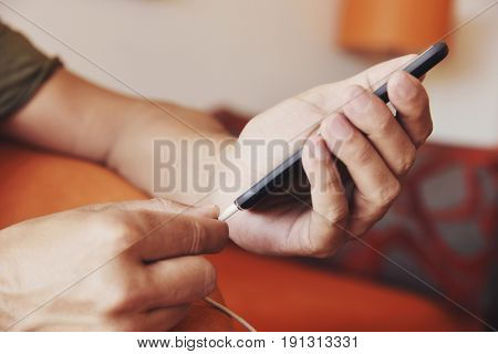 closeup of a young caucasian man plugging a cable to his smpartphone
