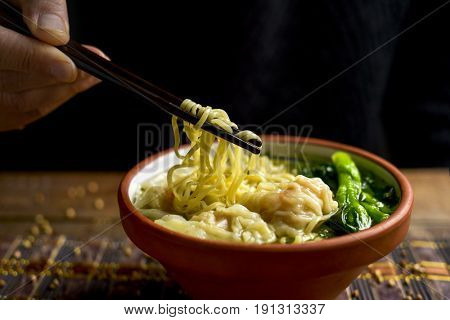 closeup of a young man getting some noodles with his chopsticks from an earthenware bowl with shrimp wonton noodle soup with choy sum, placed on a table set for lunch or dinner