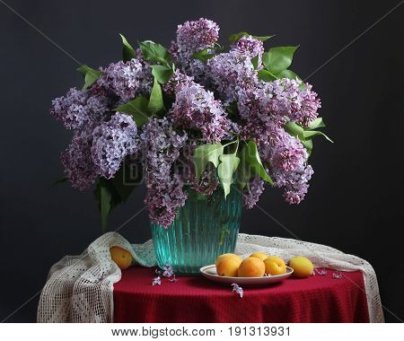 Bouquet of purple lilac in a blue vase and apricots on the plate on a round table with a red tablecloth against a dark background.