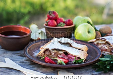 Strudel with apples and strawberries. Pie with apples and strawberries summer pie. Summer breakfast in nature.