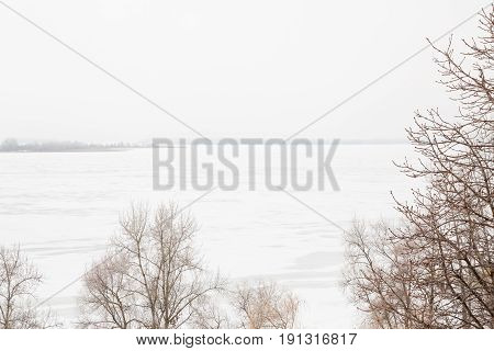 Winter river landscape. Volga. Neighborhood of the city of Saratov, Russia. The freeze-up. The trees in the foreground, the island in the background