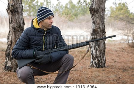 Caucasian Man Sits In Winter Forest With A Shotgun. Hunting With A Shotgun