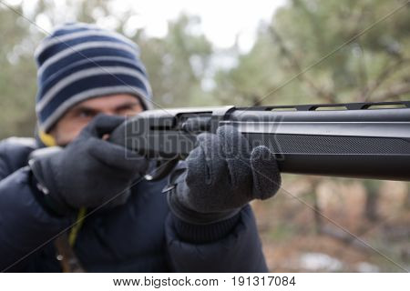Caucasian Male In Winter Forest Takes Aim. Hunt With A Shotgun