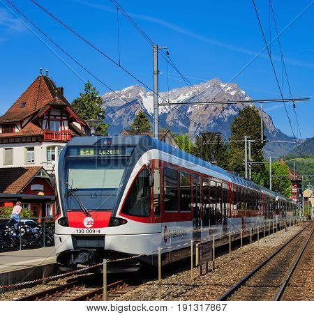 Stans, Switzerland - 8 May, 2016: a passenger train heading to the city of Lucerne at a platform of the Stans railway station, Mt. Pilatus in the background. The town of Stans is the capital of the Swiss canton of Nidwalden.