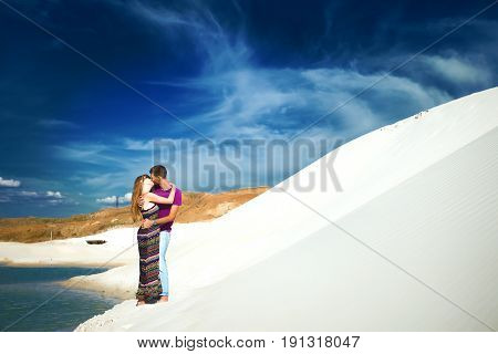 happy couple on romantic travel honeymoon vacation summer holidays romance. Young happy couple on the beach with white sand, caucasian woman and man embracing and kissing