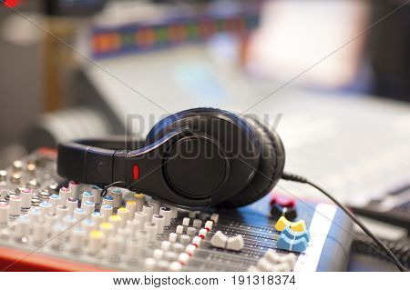 Closeup of headphones with cord on sound mixer in radio studio