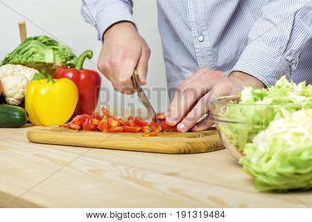 Hands of a man chopped red bell pepper for salad on a board, close-up