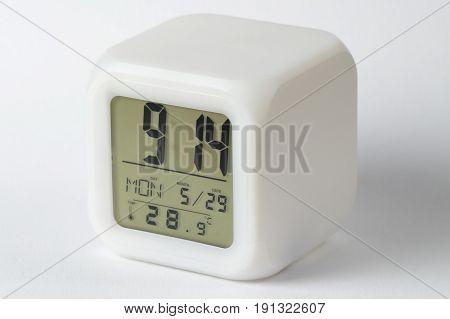 White digital alarm clock over white background