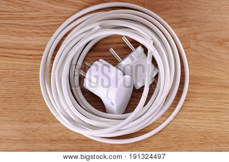 White cable with pair of a plugs on a wooden table.
