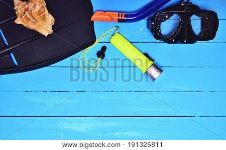 Flippers mask and tube for scuba diving on a blue wooden background top view an empty space
