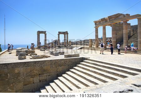 RHODES ISLAND, LINDOS, GREECE, JUN 22, 2013: View on famous antique greek temple ruins on the rock on Greece island Rhodes in Lindos city and walking  tourists. Famous sightseeing places
