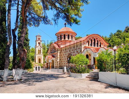RHODES ISLAND, GREECE, JUN 28, 2015: Beautiful traditional Greek church monastery Saint Nektarios with bell tower among green trees. Famous Greece islands vacations sightseeing tours