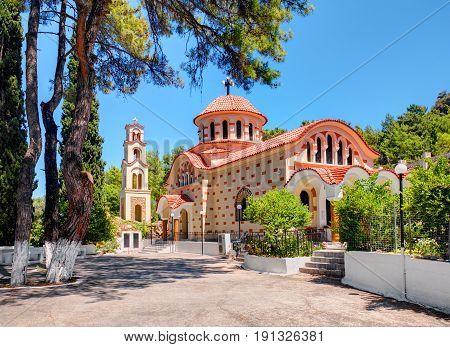 RHODES ISLAND, GREECE, JUN 28, 2015: Beautiful traditional Greek church monastery Saint Nektarios with bell tower among green trees. Famous Greece islands vacations sightseeing tours
