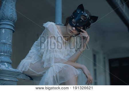 Portrait of a girl with a mask on her face sitting outdoor near the house. The girl in the mask. Posing beautiful fashion model in black cat mask.Hungry Sexual Latex Rubber Cat Black Catsuit Wint Milk