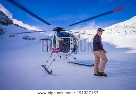 SOUTH ISLAND, NEW ZEALAND- MAY 24, 2017: Close up of helicopter and pilot waiting over the snow for hunters in South Westland's Southern Alps, New Zealand.