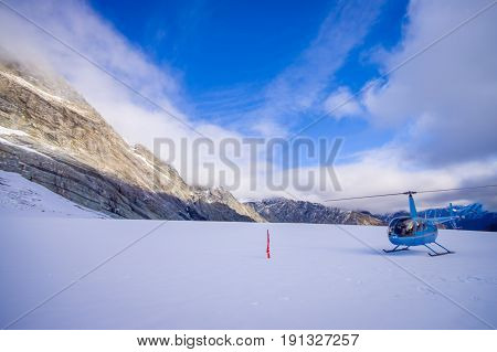 SOUTH ISLAND, NEW ZEALAND- MAY 24, 2017: Helicopter and pilot waiting over the snow for hunters in South Westland's Southern Alps, New Zealand.