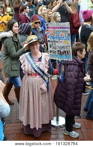 ANN ARBOR MI - JAN 21: A protester dressed as a suffragette demonstrates at the Women's March in Ann Arbor on January 21 2017.