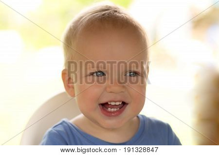 Close-up Portrait Of Cute Infant Kid Laughing And Looking At Camera