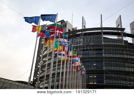 The European Parliament Building In Strasbourg, France With Flags Waving On A Evening
