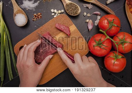 Preparing a meal. An overhead photo of a person cutting a piece of raw steak by vegetables and other ingredients.