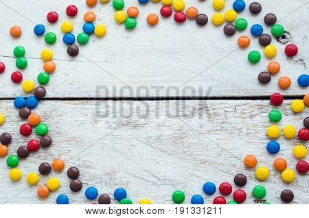 Frame from colorful chocolate coated candies texture on white wooden background. Top view. Copy space.