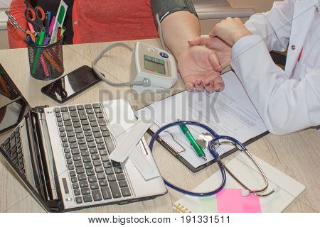 medicine age health care and people concept - close up of doctor with tonometer checking senior woman blood pressure level at hospital