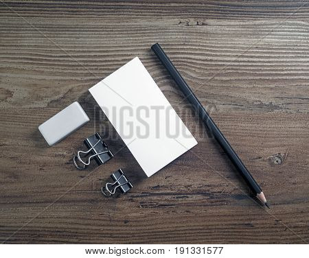 Blank business cards pencil and eraser on wooden background. Mockup for ID. Template for branding identity. Top view.