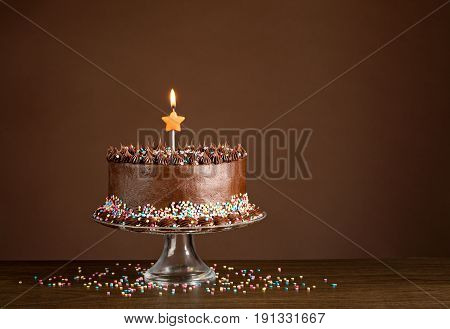 Chocolate birthday cake with colorful sprinkles and candles over a brown background.